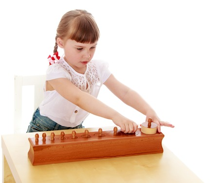 montessori: Passionate about the little blonde girl with short bangs and long braids white t-shirt with short sleeves sits at his Desk, intently studying Montessori material girl with her friends would be going to a Montessori kindergarten-Isolated on white backgroun