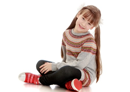 Beautiful girl with short bangs and long braids in a striped knitted jumper is sitting on the floor Stock Photo