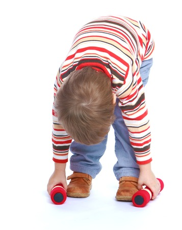 bent over: very little boy in a striped shirt and blue jeans bent over to pick up two dumbbells