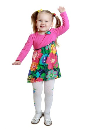 chubby girl: Joyful little chubby girl with braided hair in a ponytail in colorful dress and white stockings jumps