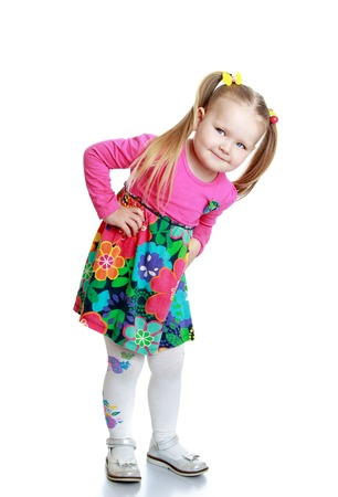 little blonde girl: Joyful little chubby girl with braided hair in a ponytail in colorful dress and white stockings bent over
