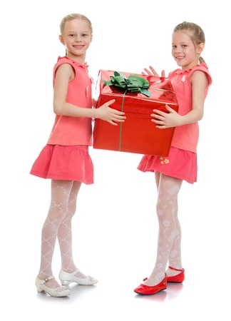 giftwrapped: Two cute girls girlfriend in pink shirts and short pink skirts grabbed from all sides large gift-wrapped box tied with a bow