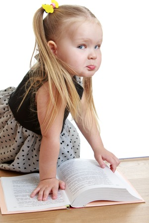 Adorable little round-faced girl with a long ponytail on her head sits on the floor and reading a thick book Stock Photo