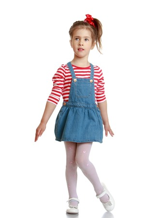 denim skirt: Adorable little blonde girl with braids braided hairstyle in a striped t-shirt and short denim skirt is lifting her leg