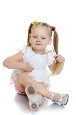tied girl: Adorable little blonde girl with her hair braided into pigtails that are tied with colored rubber bands, white shirt and pink shorts is sitting on the floor Stock Photo