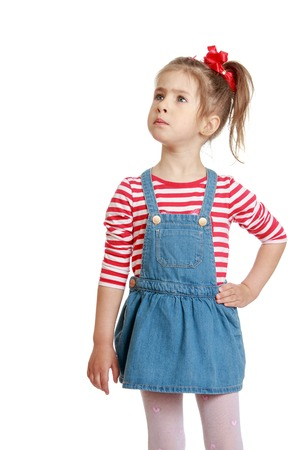 denim skirt: Adorable little blonde girl with braids braided hairstyle in a striped t-shirt and short denim skirt looks toward a larger plan Stock Photo