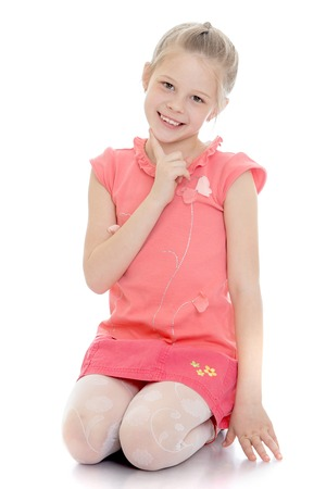 short skirt: Laughing little girl in a pink t-shirt with short sleeves and a short skirt on her knees cute looking at the camera
