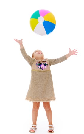 throw up: Joyful little girl in a long gray dress throw up a large inflatable striped ball