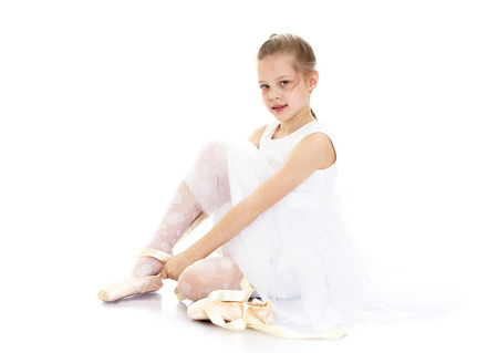 transparent dress: Beautiful blond little girl ballerina in white transparent dress sitting on the floor and puts on foot in Pointe shoes