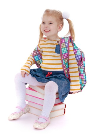 denim skirt: Adorable little blonde girl with long tails on the head in which braided pigtails wears a striped sweater and long denim skirt sitting on stack of books