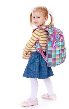 denim skirt: Smiling little blonde girl with long tails on the head are braided bows. The girl is dressed in a striped jumper and blue denim skirt with the back hanging on her school backpack . The girl turned toward the camera sideways-Isolated on white background