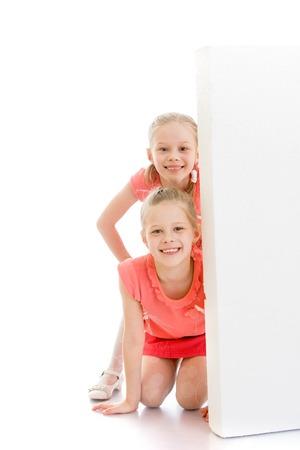 gimnasia ritmica: dos riendo hermanitas chicas en ropa de color rosa, que mira furtivamente de detr�s de obst�culos-Aislado en el fondo blanco