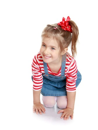 pretty little girl: cute beautiful little blonde girl with the bow on her head in a striped t-shirt with long sleeves and a denim short skirt and white stockings crawls on her knees