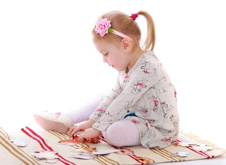 Schattig klein meisje met een paardenstaart op haar hoofd in een lange katoenen jurk zit op de mat in een Montessori kleuterschool. Het meisje gaat door de handen van de kaart-geïsoleerd op een witte achtergrond Stockfoto