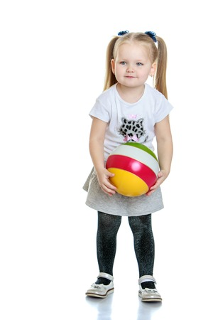 Beautiful little round-faced girl with long tails on the head are braided bows is dressed in a white t-shirt with short sleeves and short pleated skirt holding a small striped rubber ball