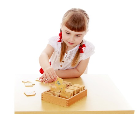 montessori: Charming blonde little girl with long braids sits at a table study mathematics in Montessori kindergarten Stock Photo