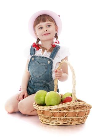jugo de frutas: Alegre hermosa niña en un sombrero de color rosa y una camisa de mezclilla y blancas overoles de manga corta que se sientan en el suelo y mantenga la cesta tejida a mano