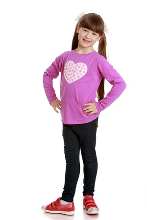bangs: Beautiful girl of school age with very long bushy tails on the head and short bangs bravely standing in front of the camera wearing a pink shirt and long black pants