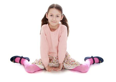 petite fille avec robe: Charmante jeune fille mince avec de longues queues sur la tête et un pull rose assis sur le sol