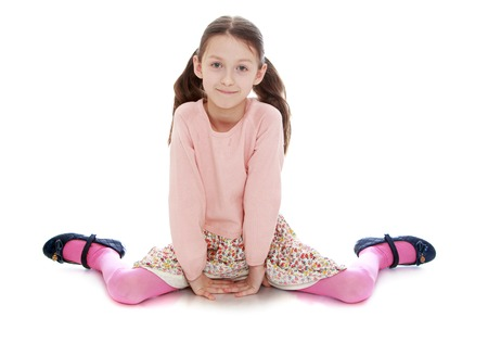 single child: Charming slim girl with long tails on the head and a pink sweater sitting on the floor