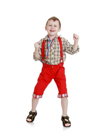 red shorts: Cheerful, joyful little boy in a plaid shirt and long red shorts