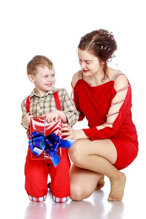 red shorts: Cheerful, joyful little boy in a plaid shirt and long red shorts woman holding a wrapped box decorated with a bow Stock Photo