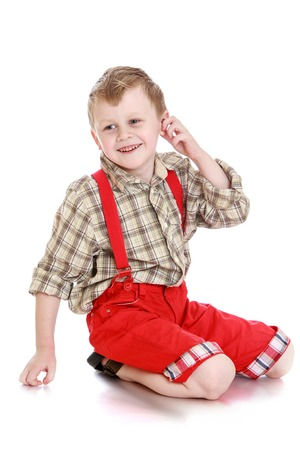 red shorts: Joyful blond little boy plaid shirt long sleeve long bright red shorts sitting on his knees on the floor. Boy hand touches his ear and looks aside-Isolated on white background
