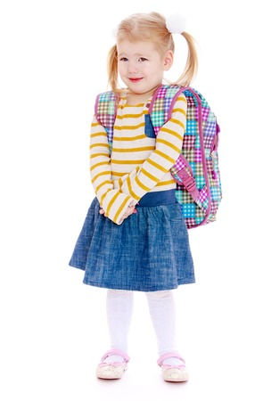 denim skirt: Adorable little blonde girl with short bangs and long bunches carries on his shoulders a large school bag. On the girl wearing a striped sweater short denim skirt. Girl goes to school for the first time and is very worried-Isolated on white background