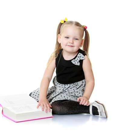 adhere: Beautiful little girl with long blonde bunches that adhere colorful erasers. Girl sitting on the floor or turn the pages of thick books. She will soon go to school-Isolated on white background Stock Photo