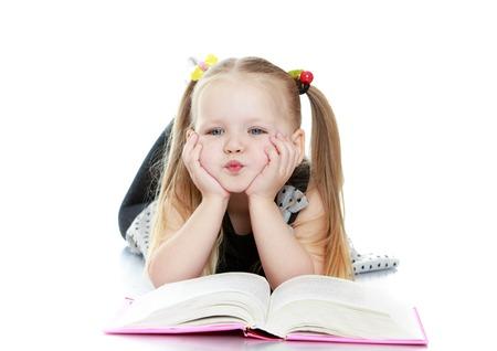 長い金髪を持つ美しい少女は、カラフルな消しゴムを準拠する房します。厚い本を読んで彼女の腕に寄りかかって床に横たわった少女。どうやらこ 写真素材