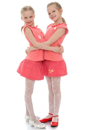 Two charming little girls sisters hug each other. The girls dressed in red T-shirts with short sleeves and short red skirt. Girls twins are very similar to each other-Isolated on white background