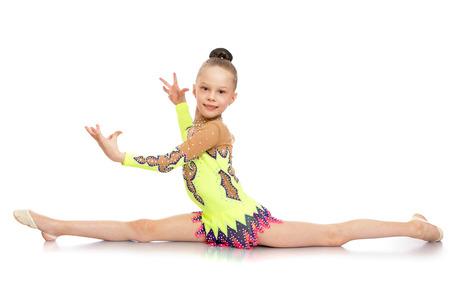 gimnasia: Delgado atleta chica muy joven con el pelo peinado en una bola que se sienta en las divisiones. Una niña vestida con un hermoso deporte traje de baño aislado contra el fondo blanco