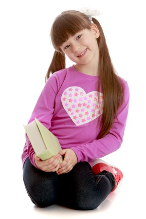 beautiful bangs: Beautiful girl with long tails on a short-cut bangs his head sits on her knees on the floor. The girl is holding a thick volume which she reads during the summer holidays. A girl wearing a red sweater with long sleeves and black jeans.-Isolated on white b