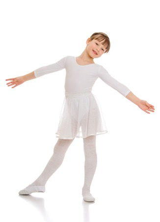 elegantly: Adorable little ballerina in a white suit dancing. Girl elegantly her arms to the side and smiling at the camera-Isolated on white background Stock Photo