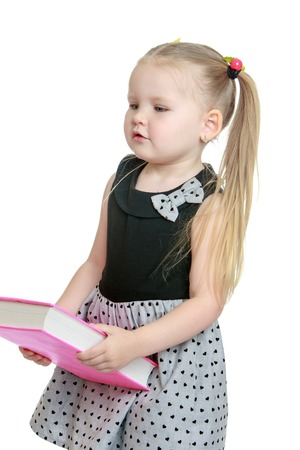 Cute little blonde girl with long tails on the head , which adheres to multi-colored gum. The girl is holding in front of him a thick book which shell be in school. The girl dressed in a short grey dress, close-up-Isolated on white background