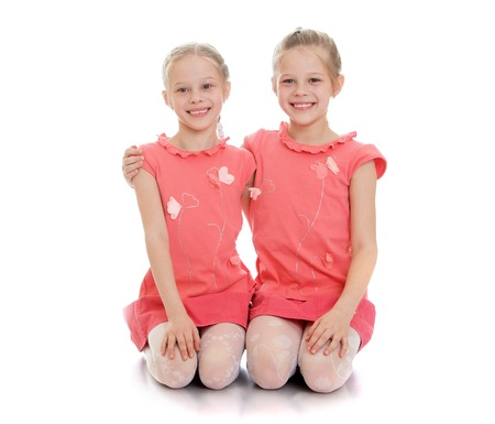 two cute twin girls sitting on the floor and hug. The girls are very happy that they came with his parents to a Studio shoot. The girls are dressed in pink clothes.-Isolated on white background Stock Photo