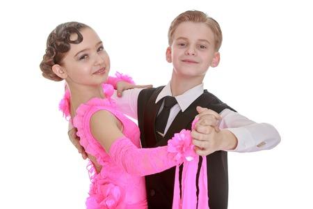 Mooie jeugd danspaar. het meisje is gekleed in een lange roze jurk en een jonge man in een zwarte drie. Beiden hand in hand en kijken naar de camera-Geïsoleerd op witte achtergrond Stockfoto