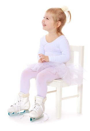 sweater girl: Cute little girl in a white tracksuit sits on the chair and looks away. On the feet of the girls are wearing skates. Girl in school figure skating choreography. Her mom every day goes to school figure skating-Isolated on white background