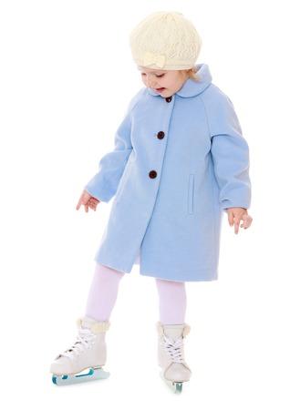 patinaje sobre hielo: Niña linda en un chándal blanco que se coloca en el hielo en un abrigo de lana azul. A los pies de las niñas están usando patines. Chica en la figura de la escuela de patinaje coreografía. Su mamá todos los días va a la figura de la escuela de patinaje, aislado en fondo blanco