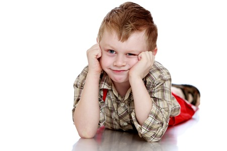 red shorts: Playful little boy in a plaid shirt and long red shorts lying on the floor clutching her head-Isolated on white background