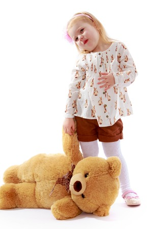 playing with spoon: Pretty little blonde girl in brown shorts and a white t-shirt holds the paw of a Teddy bear. lying on the floor-Isolated on white background