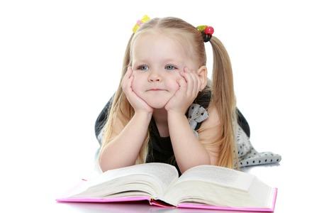 Schattig klein mollig, blond meisje met lange staarten op het hoofd ligt op de vloer leunend op zijn handen. Een meisje dat een boek en dromen van de opvoeding van haar naar de top van de leest eye-Geïsoleerd op witte achtergrond Stockfoto