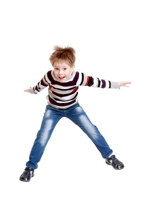cute little boy: Funny little boy in a striped shirt and blue jeans jumps high spreading their arms Stock Photo