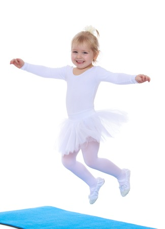 ballerina costume: Adorable little blonde girl ballerina in white costumes fun jumping on blue mats spread wide his arms-Isolated on white background