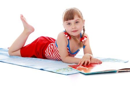 petite fille maillot de bain: Adorable petite fille blonde avec des nattes tress�es sur la t�te, dans un maillot de bain rouge bronzer sur une serviette et lire un livre-isol� sur fond blanc