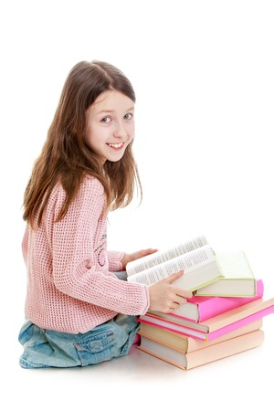 denim skirt: Cheerful little girl with flowing long hair, wearing a pink sweater and blue denim skirt sitting on the floor. The girl sees the book-Isolated on white background