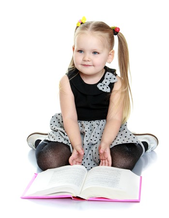 Beautiful little round-faced girl with long ponytails on her head sitting on the floor and reading a book. A girl wearing a long cotton dress -Isolated on white background Stock Photo