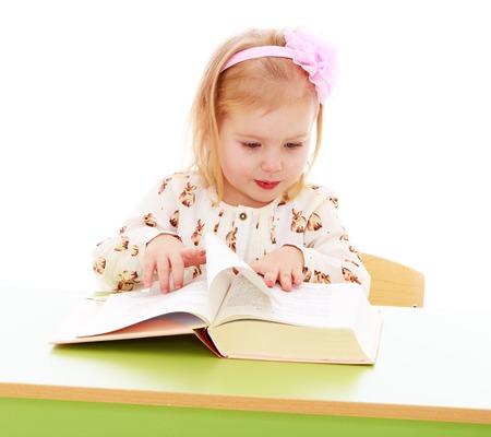 cute babies: Ni�a hermosa en un jard�n de infantes Montessori est� sentado en su escritorio. La muchacha que lee cuidadosamente un libro de texto de espesor hojeando las p�ginas. La ni�a est� probablemente en busca de las im�genes en el libro. Primer-Aislado en el fondo blanco