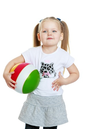 Cute little round-faced girl with long braided hair in a ponytail holding a ball. The girl dressed in a short grey skirt and a white shirt with a pattern. the girl holds her hand over her stomach . Closeup-Isolated on white background
