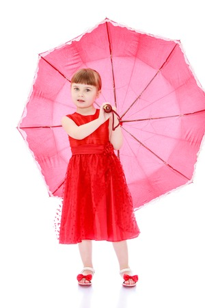 umbrela: Beautiful little blonde girl with short bangs and long braids on his head. A girl wearing a long red holiday dress . Girl holding a red umbrella-Isolated on white background Stock Photo